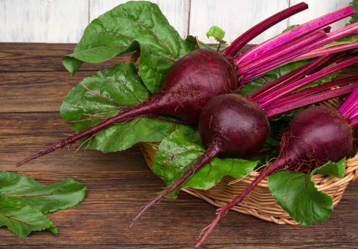 fresh organic beetroot with leaves on wooden table